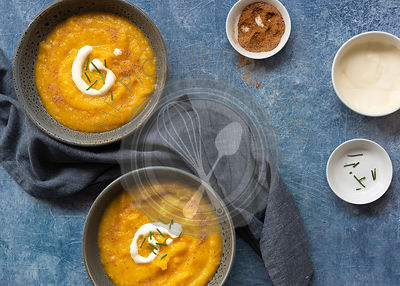 Two bowls of thick homemade pumpkin soup with small bowls of chives, cream and nutmeg.