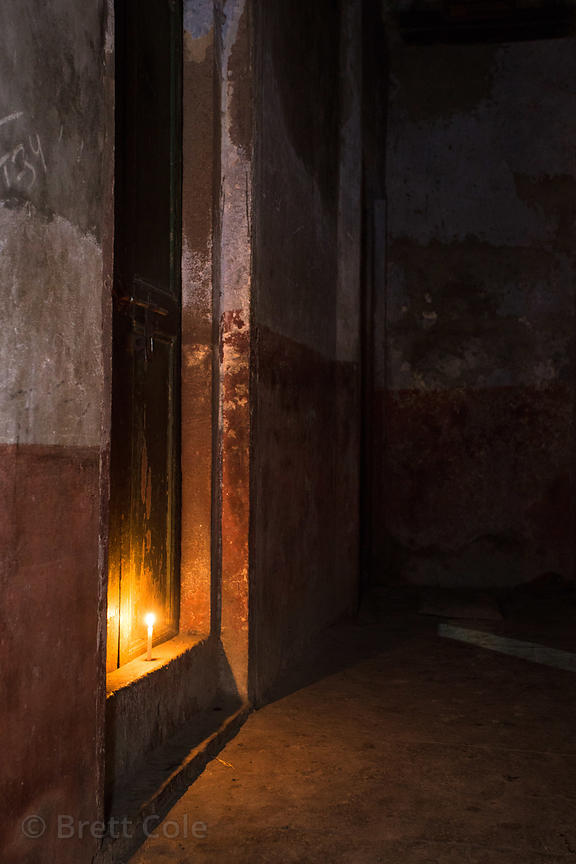 A candle gently illuminates a doorway, Tripura Bhaliwi, Varanasi, India