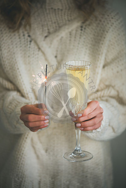 Woman in sweater holding champagne and sparkler in hands, close-up