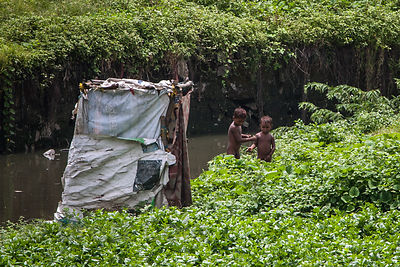 Boys on an impoverished homestead in a field in Bandra, Mumbai, India.