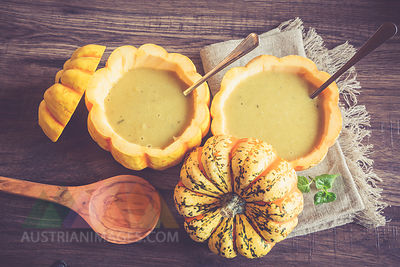 Creamed pumpkin soup in hollowed chameleon pumpkins on cloth and dark wood