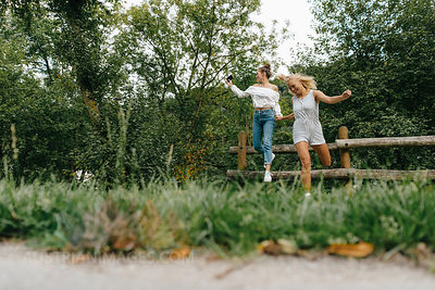Two happy young women jumping from fence in a park