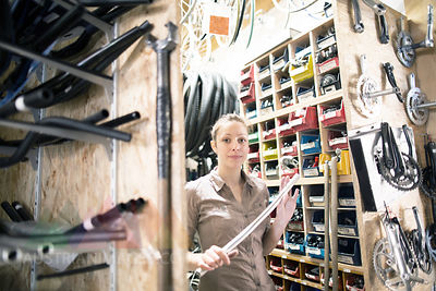 Young woman in a bicycle repair shop holding rod