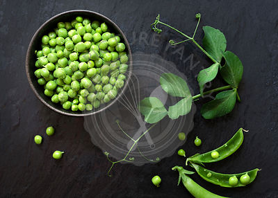 Freshly shelled organic green peas in a bowl beside opened pods.