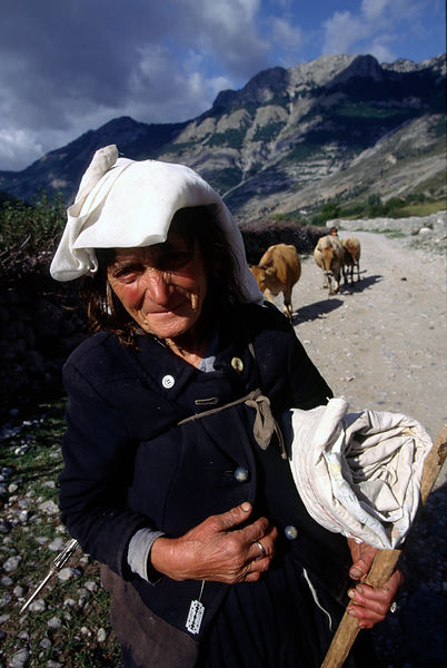 A woman in traditional dress on the road to Thethi