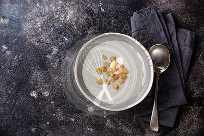 Vichyssoise cream soup in bowl with croutons on dark background copy space