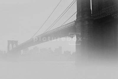 An atmospheric image of the Brooklyn bridge and the Hudson river on a misty morning.