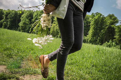 Woman walking with flowers on meadow