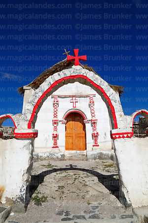 Entrance archway and facade of rustic church in Cotasaya village, Region I, Chile