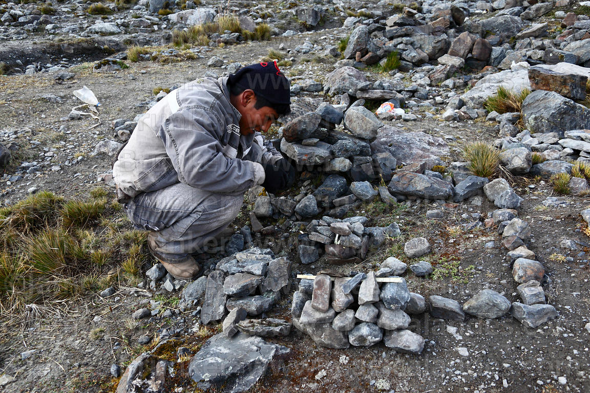 A young man arranges stones in the form of a house and plot of land before a challa / blessing ceremony, Qoyllur Riti festiva...