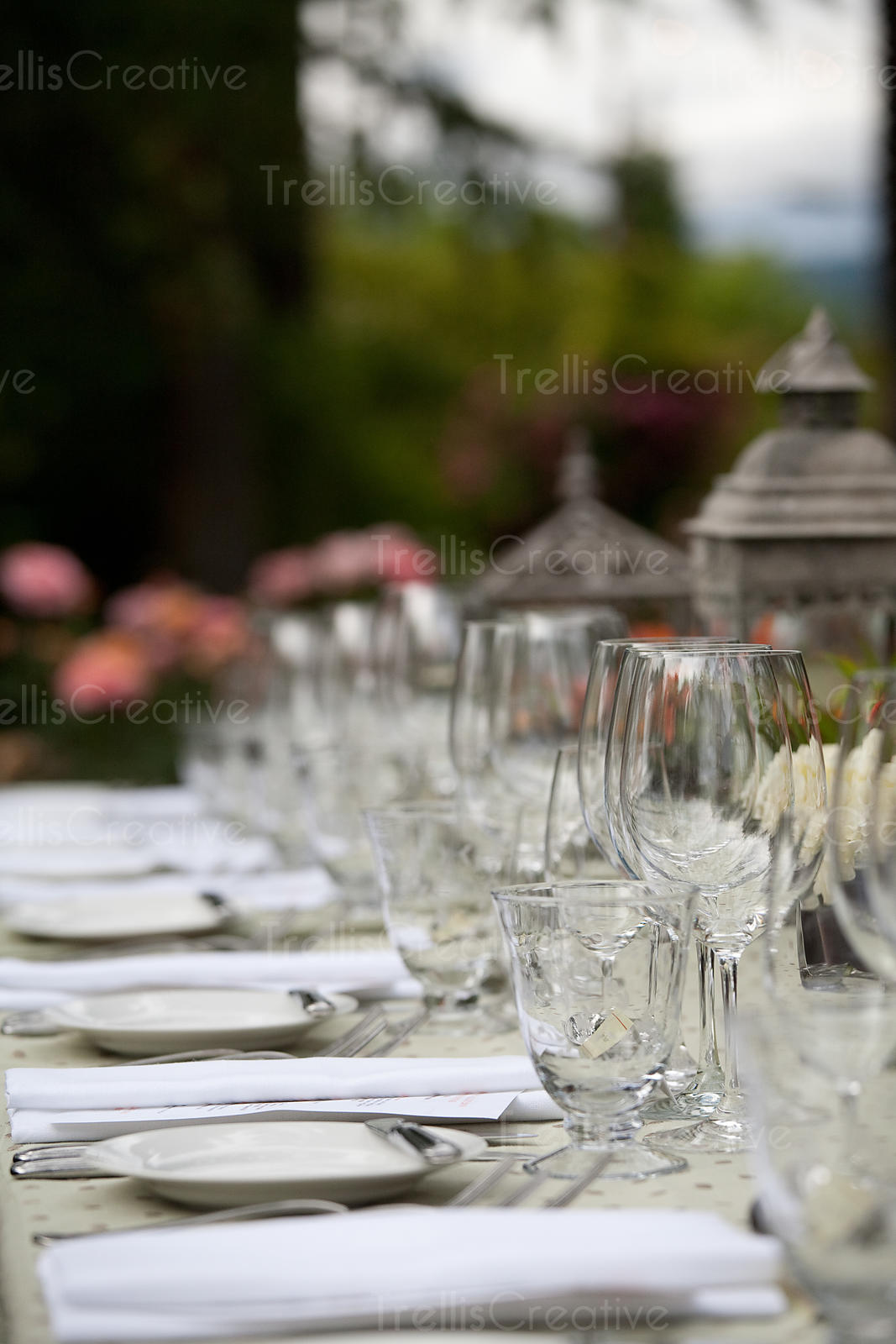 Looking across an elegantly decorated table at an outdoor wedding reception