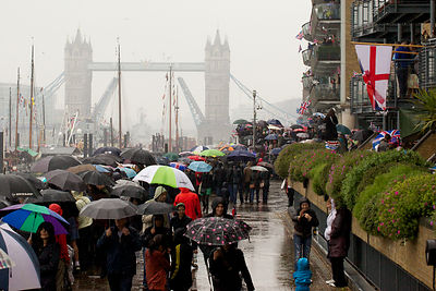 Crowds Stand in Pouring Rain Watching the Thames River Pageant