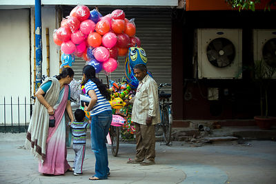India - New Delhi - Ram Pal Gupta wwaits in a local market for a middle class family to buy his balloons