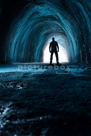 An Atmospheric image of a mystery man standing in a cave.