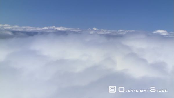 Flying alongside billowing cumulus, passenger POV