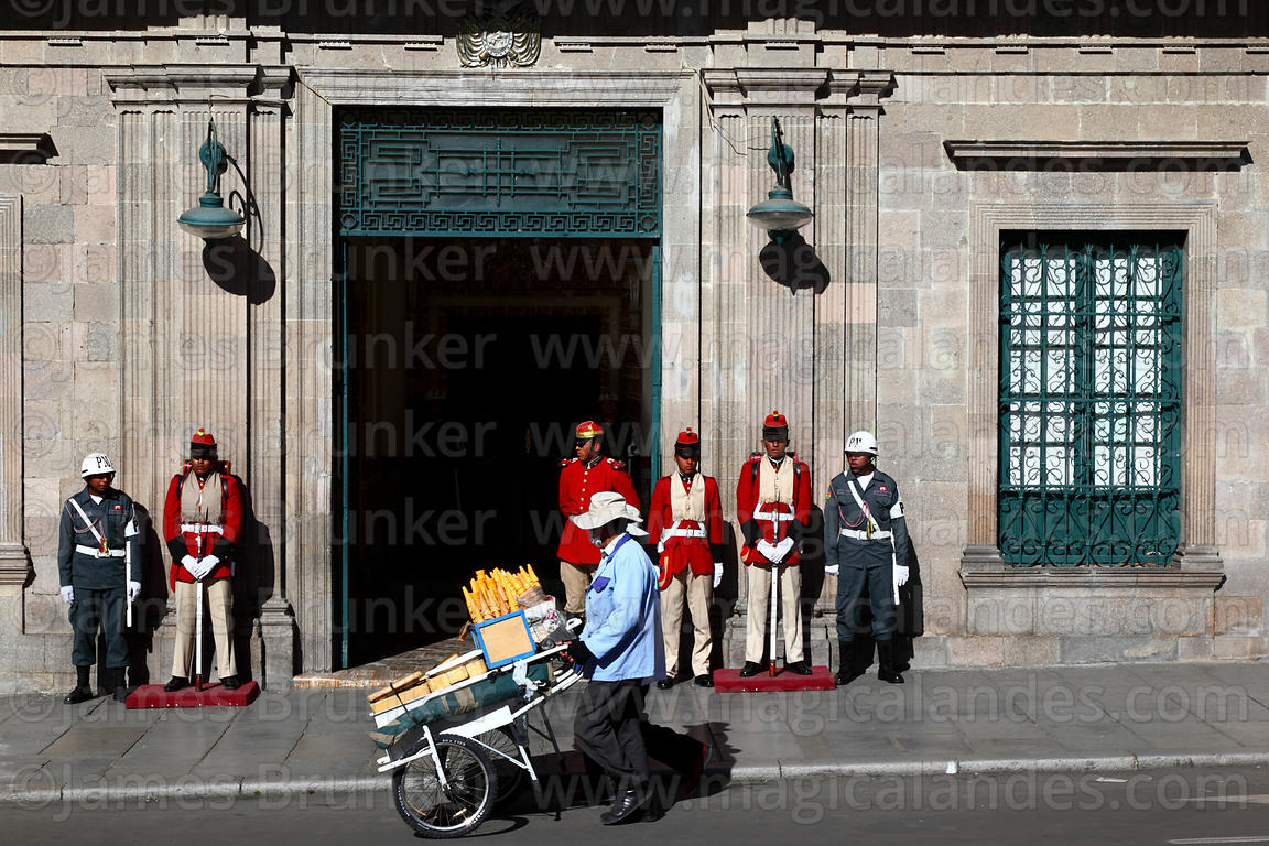 Man pushing ice cream cart past Los Colorados guards and entrance of Presidential Palace, Plaza Murillo, La Paz , Bolivia