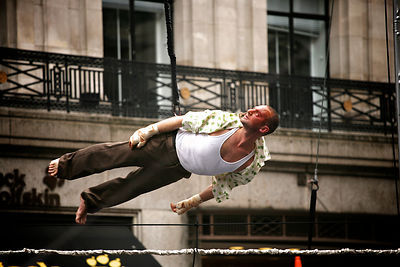 Circus performer suspended horizontally during a show in Regent Street, London