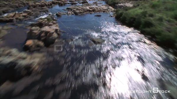 Aerial shot over a rocky river then over the edge of a cliff to a river canyon and waterfalls Sabie. Mpumalanga South Africa