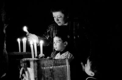 Lebanon - B'Charre - A woman and her grandchildren light candles in the grotto of Deir Mar Elisha