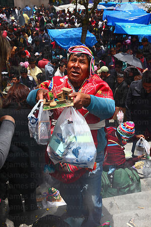 A yatiri or shaman recites prayers as he blesses miniatures, Alasitas festival, La Paz, Bolivia