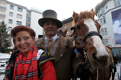Schlitteda Event with traditional costumes and horses in Engadine.