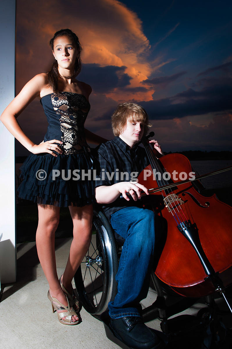A young man ply cello from a wheelchair by the lake in the evening