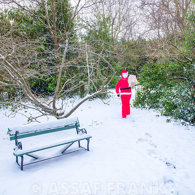 Santa Claus with gift sack walking through snow covered winter forest