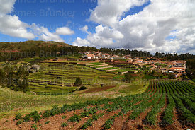 View of potato field, village, and terraces of Inca site, Chinchero, near Cusco, Peru