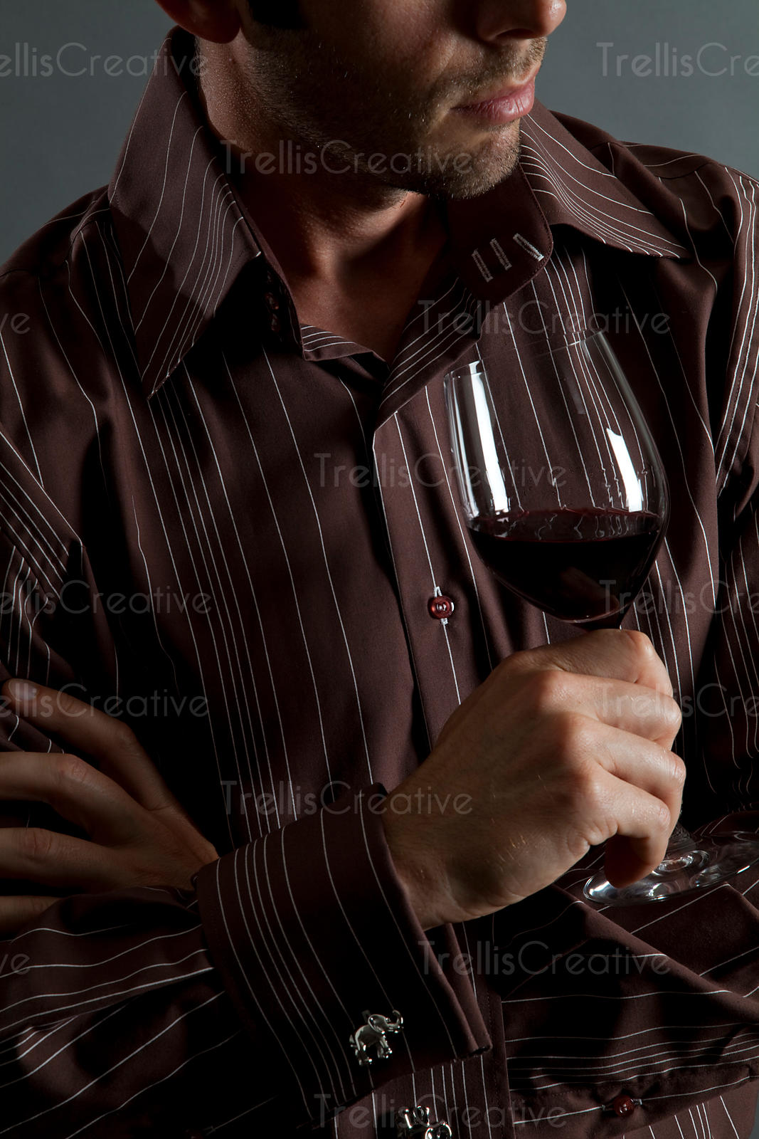 Close-up of a young man holding a glass of red wine