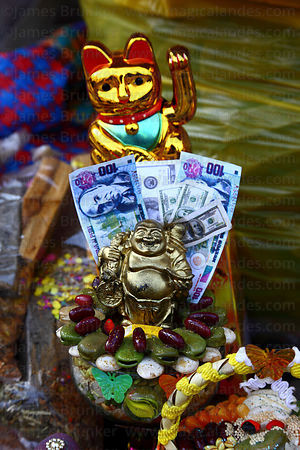 Miniature laughing buddha, bank notes and maneki-neko / beckoning cat for sale in market for Alasitas festival, Puno, Peru