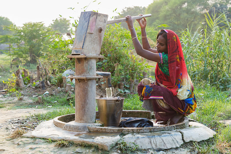 Woman Pumping Water from a Village Well