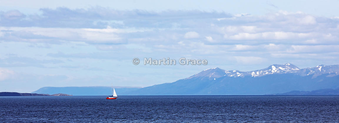 The Beagle Channel, Ushuaia, with a single red sailing boat, Tierra del Fuego, Argentina