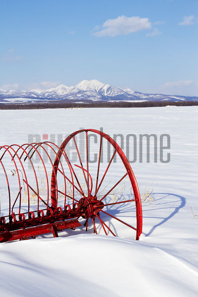 Farm implement and Mount Shari in Snowy Landscape