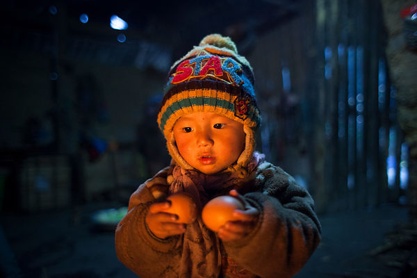 Enfant de 4 ans contemplant le feu dans une cuisine à Bac Ha, Vietnam / 4 years old child contemplating fire in a kitchen in ...