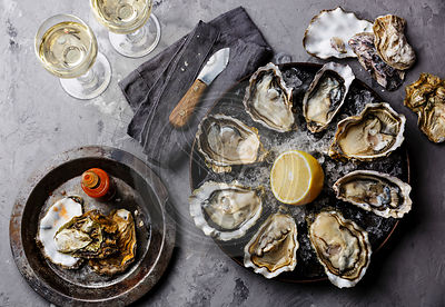 Opened Oysters Fines de Claire on plate with spicy sauce and white wine on gray concrete texture background