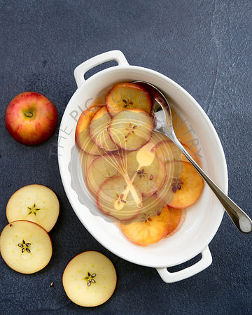 A spoon in a serving dish filled with slices of honeyed apples in syrup.