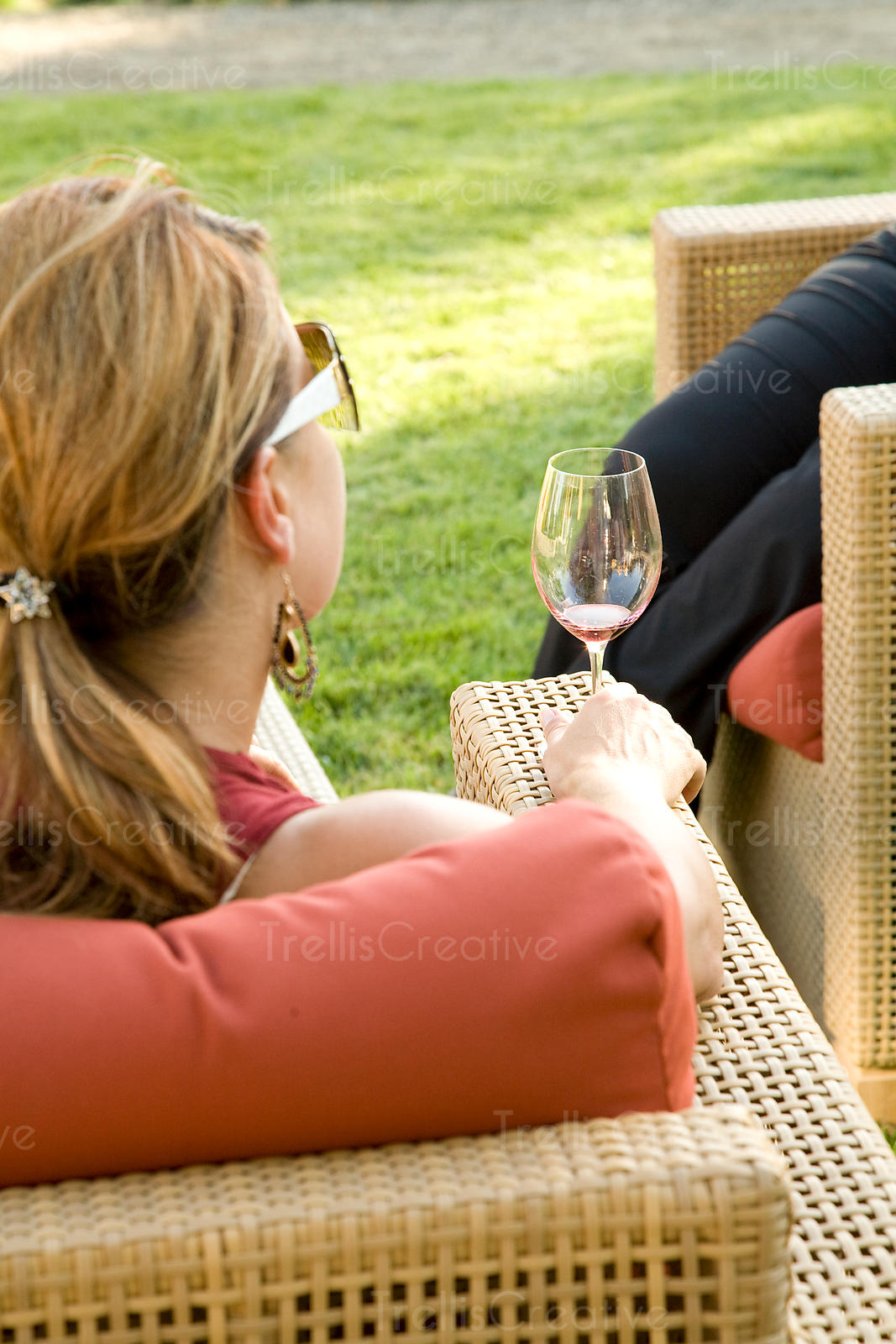A young woman sits on an outdoor patio drinking a glass of wine
