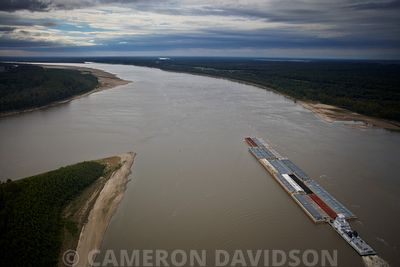 Aerial photograph of a tug boat pushing barges upstream in the Atchafalaya River in southern Louisiana.
