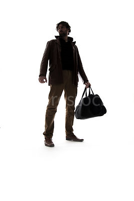 A silhouette of a man in a leather jacket, holding a bag – shot from low level.
