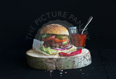 Fresh homemade burger on wooden serving board with spicy tomato sauce, sea salt and herbs over black  backdrop
