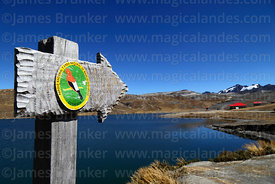 Wooden sign next to Lake Estellani with Cotapta National Park badge, La Cumbre, Bolivia