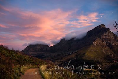 Hiker walking along a track on Lion's Head, with a view of pink clouds over Table Mountain in the background