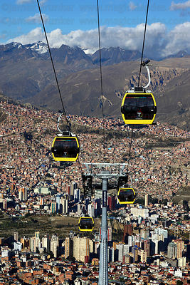 Yellow Line cable car gondolas above Sopocachi in La Paz city centre, Cordillera Real mountains in background , Bolivia