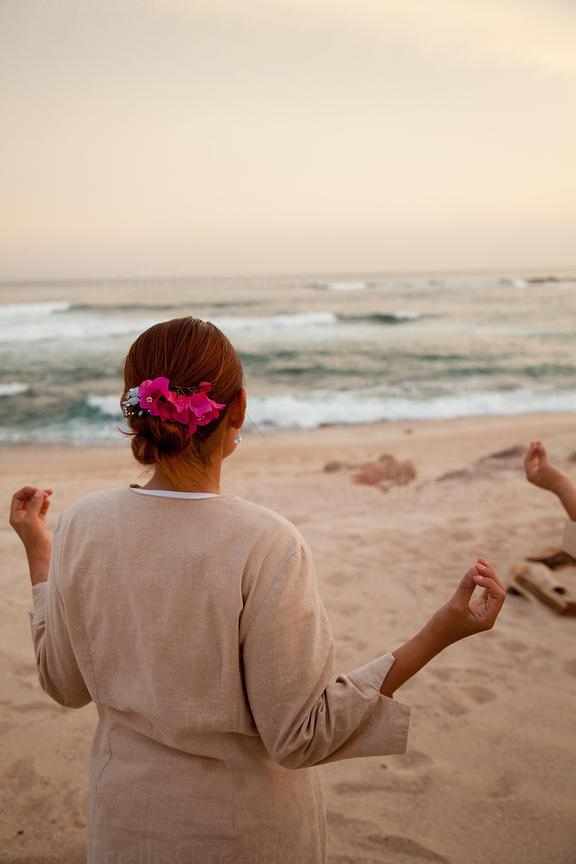A young woman practices yoga on the beach
