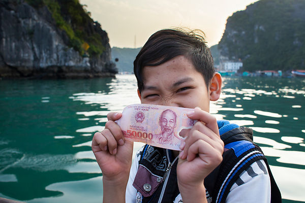 Tué , 12 ans, montre le billet qu'il a gagné en vendant un poisson qu'il a pêché, Baie de Lan Ha, Vietnam / Tué, 12 years old, shows the notes he earned by selling a fish he fished, Lan Ha Bay, Vietnam
