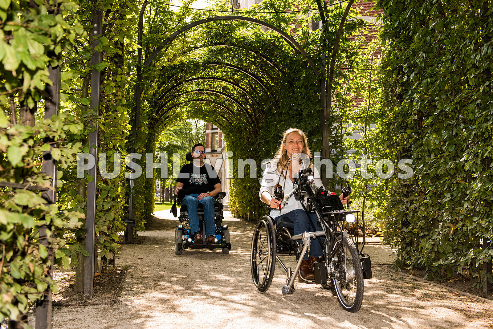 Couple using power wheelchairs under a garden arbor