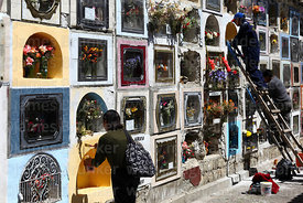 Woman painting tomb in cemetery for Todos Santos festival, La Paz, Bolivia