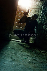 An atmospheric image of the silhouette of a mystery man crouching with a gun at the bottom of some cellar steps.