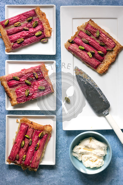 Pieces of rhubarb and pistachio nut tart on dessert plates with a bowl of cream.