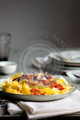 A typical italian dish pappardelle pasta with tomato sauce, olives and parmesan on wooden table